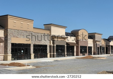A suburban shopping center under construction, made to appear like a small town street.  Empty storefronts.