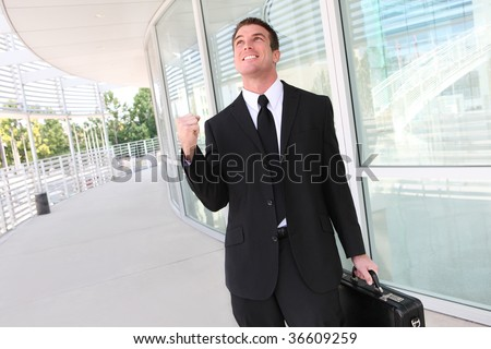 A successful business man  with fist clenched in victory - stock photo