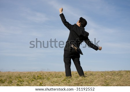 A successful business man with his arm outstretched on a field