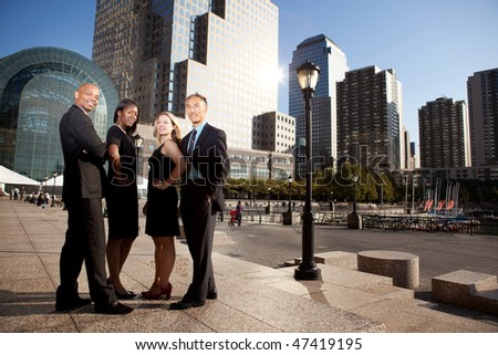 A successful business team in an outdoor setting against a city background - stock photo