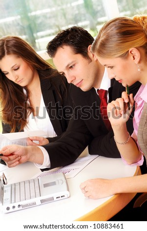 a successful business team is working on a table with documents and a laptop - stock photo