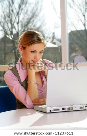 a successful business woman is working on a table with a laptop - stock photo