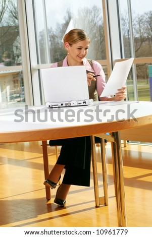 a successful business woman is working on a table with a laptop with documents - stock photo