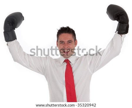 A successful businessman holding boxing gloves up symbolizing conflict or winning a battle - stock photo