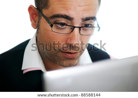A successful businessman with glasses wearing vest and pink shirt looking at a little computer