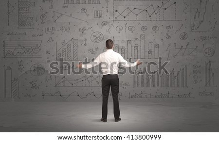 A successful confident businessman thinking about decisions, standing in front of wall full with graph pie charts and calculations concept - stock photo