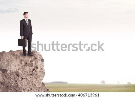 A successful good looking business person standing on top of a high cliff above country landscape with clear white sky concept - stock photo