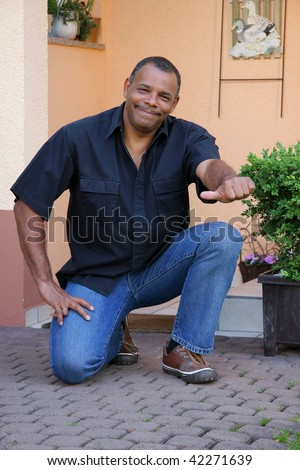 a successful, happy and powerful African-American photographed in the summer sun in front of his house posing with the thumbs up sign while kneeling down - stock photo