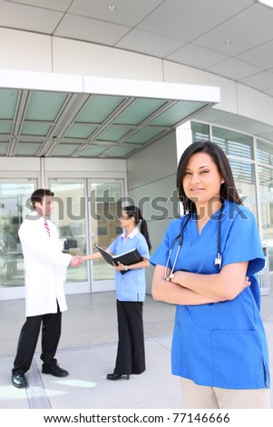 A successful man and woman medical team outside hospital - stock photo