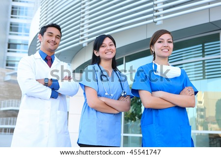 A successful man and woman medical team outside hospital building - stock photo