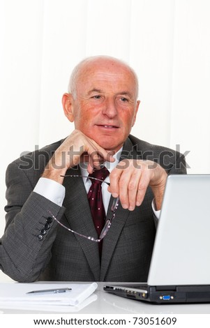 A successful older businessman sits in his office with a laptop.