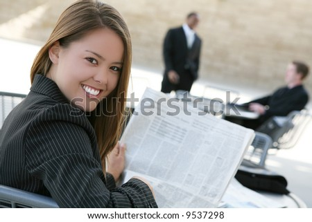 A successful, pretty business woman reading the newspaper - stock photo