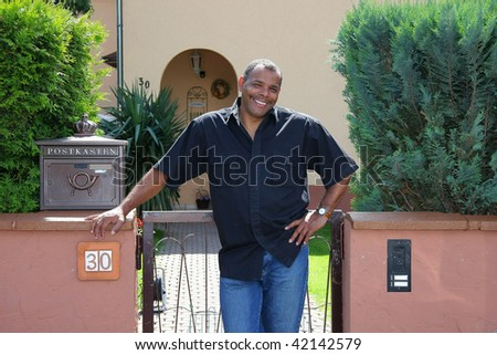 a successful, smiling and happy African-American man standing in front of his house, photographed in the summer sun - stock photo