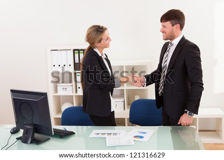 A successful smiling business man and woman stand in an office behind a table shaking hands as they successfully conclude a deal - stock photo