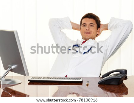 A successful young doctor sitting at desk and smiling. - stock photo