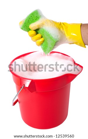 A sudsy bucket or pale of soap with a hand holding a sponge. cleaning concept or chores - stock photo