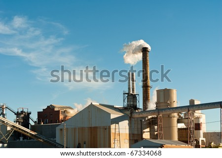 A sugar mill factory emitting steam into the sky. - stock photo