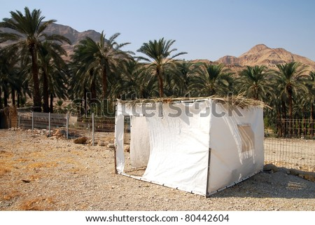 A sukkah in the desert. A sukkah is a temporary hut constructed for use during the week-long Jewish festival of Sukkot. It is topped with branches and often the interior is decorated. - stock photo