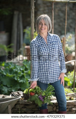 a summer day, a middle-aged woman is standing near stone wall in the garden with his basket full of vegetables and flowers. she is surrounded by plants and by garden tools