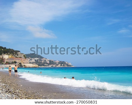 A summer day on the beach in Nice France.  Near the Promenade des Anglais. tourists, sun bathing and swimming on summer hot day. - stock photo