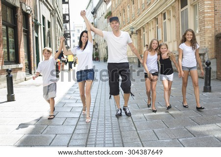 A Summer family portrait of parents and kids outside in urban style - stock photo