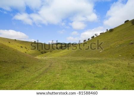 a summer landscape with a view along a steep grassy valley under a blue sky with white clouds - stock photo