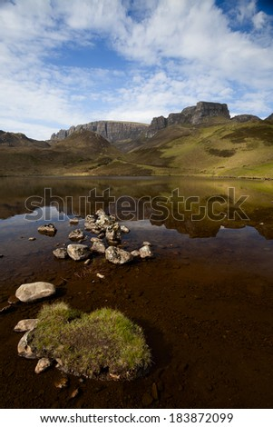 A summer scene with an unnamed lake in the Scottish Highlands in front of the Trotternish ridge peninsula. All at th isle of Skye, Scotland. - stock photo