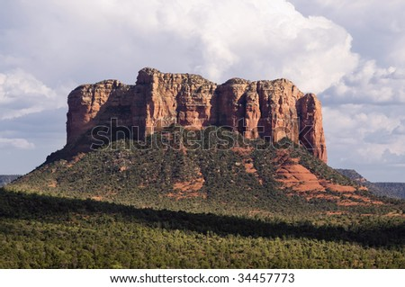 A summer storm and sunny cloud covering producing dramatic lighting over spectacular Sedona red rock landscape. - stock photo