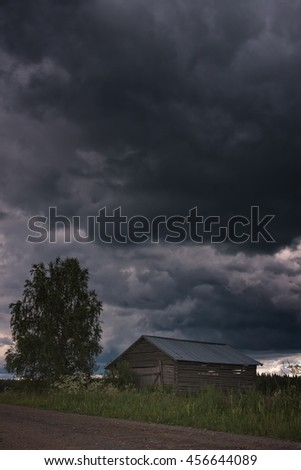 A summer storm is coming over the fields of the Northern Finland. The small barn stands on the fields ready for the bad weather.
