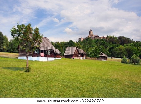 A summertime view of authentic, centuries old folk houses in the state-owned open-air museum of Stara Lubovna, Spis region, eastern Slovakia. Famous castle of Lubovna can be seen in the background.