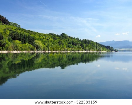 A summertime view portraying forests of Bobrovnik reflected in the deep waters of Liptovska Mara. The mountains of Rohace, part of Western Tatras, can be seen in the distance.