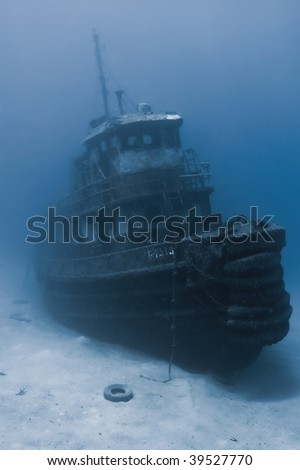 "A sunken tugboat emerges out of the gloomy water.... located in ""Wreck Alley"" of Cooper Island, BVI's."