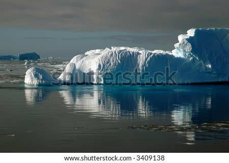 A sunlit Antarctic iceberg in the Southern Ocean in a calm sea covered by ice floes. It beautifully reflects in the water. Picture was taken during a 3-month research expedition. - stock photo