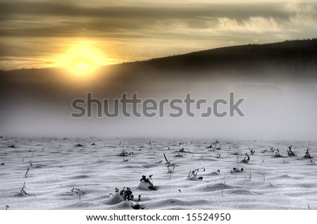 A sunrise over the valley on a misty winter morning. - stock photo