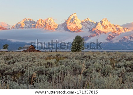 A sunrise view of the Teton mountain range, with the Moulton barn in the foreground. - stock photo