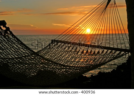 A sunset as seen through the netting of a hammock on the Big Island of Hawaii. - stock photo