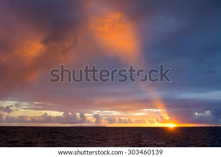 A sunset at Hanalei Beach in Kauai after a thunderstorm shows a beam of light piercing the dark clouds. - stock photo