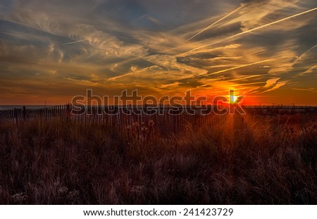 A sunset over the ocean at the beach shore in Cape May, New Jersey. - stock photo