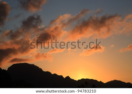 A sunset scene, with brilliant orange yellow and pink clouds against a dark blue sky, with the sihouette of hills where the sun is going down. - stock photo