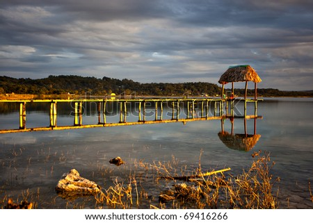 A sunset warms a dock in Guatemala - stock photo