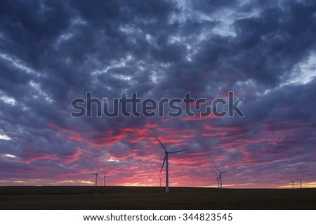 a sunset with wind farm. - stock photo