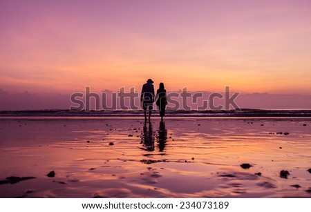 A sunset. Young couple on the beach of the Bay of Bengal. - stock photo