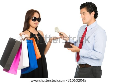 A superficial shopaholic stylish Asian female holding department store bags holds hand out to receive shopping money from her reluctant husband H - stock photo