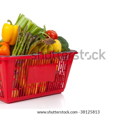 A supermarket shopping basket full of fresh vegetables on a white background with copy space