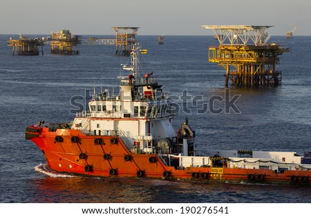 A supply vessel and rigs in an oil field  - stock photo