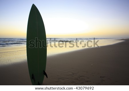 a surfboard in the sand by the beach