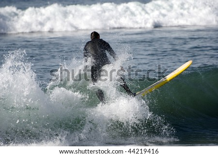 A surfer catches the wave - stock photo