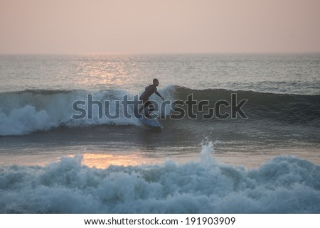 A surfer enjoys early morning waves at Nauset Beach on Cape Cod, Massachusetts. This beach is well known for its waves and white sharks. - stock photo