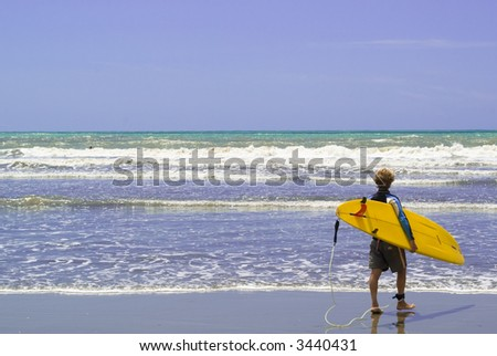 A surfer  enter into the rough sea, ready to surf. - stock photo