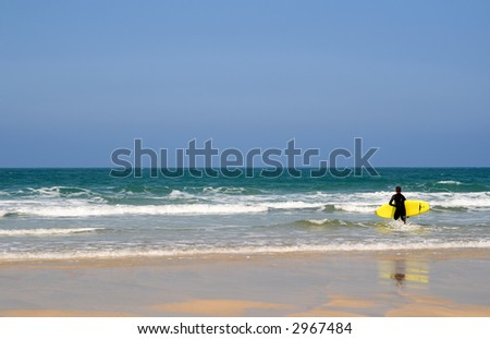 A surfer entering the sea in St. Ives, Cornwall, UK - stock photo